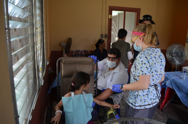 preparing to pull a tooth from a young girl with the feeding program