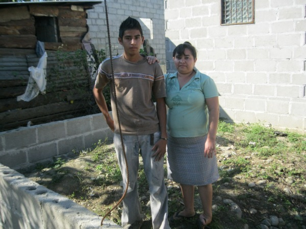 Oscar and Reyna stand within the footings of their home they began years ago.