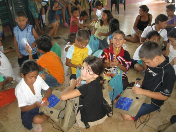 Feeling program children receive bags of donated school supplies.